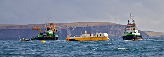 Photo of two boats installing a wave energy device in the sea